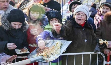 На Масленицу в России людей кормили блинами как скот из лопат ФОТО