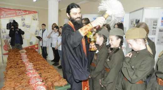 Россию охватил культ георгиевской ленточки: В Калуге священник освятил целую гору данных изделий