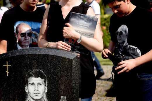 "Дети погибшего подводника с ""Курска"" на могиле отца в футболках с изображениям Путина"