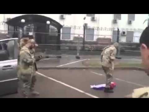 Чеченские и грузинские бойцы вытирают ноги о российский флаг возле посольства москвабада в Киеве