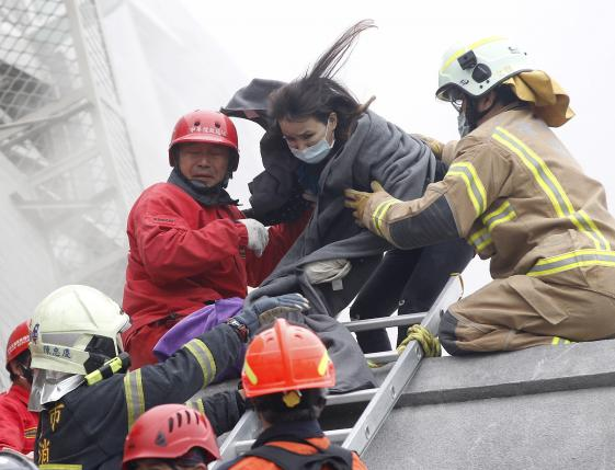 Rescue personnel help a victim at the site where a 17 story apartment building collapsed from an earthquake in Tainan, southern Taiwan, February 6, 2016. REUTERS/Pichi Chuang